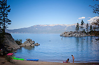 Lake Tahoe, Nevada.  Kids play on a quiet beach by the lake.