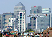 © Licensed to London News Pictures. 25/07/2012. London, UK On the day it was announced that Britain is in the longest double dip recession a Royal Navy helicopter flies in front off The City of London's Canary Wharf . Photo credit : Stephen Simpson/LNP