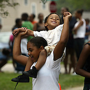 Nine-year-old Nene Prather dances to music with nephew James Benson, 2,  as they wait in line at the second annual Back to School Bash held at John R. Grubb YMCA in Des Moines, Iowa.   The first 500 students to arrive at the event received free school supplies.
