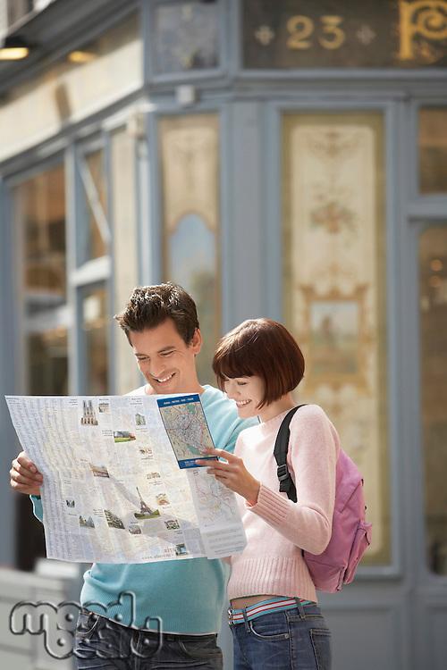 France Paris Couple reading map on street corner