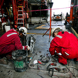 Workers with Transocean work on the drill floor of the Transocean Development Driller II rig leased by BP Plc which is drilling a backup relief well at the BP Plc Macondo well site in the Gulf of Mexico off the coast of Louisiana, U.S., on Saturday, August 7, 2010. BP successfully used the 'static kill', procedure  pumping mud into the top of the damaged well, BP plans now to finish a relief well to permanently plug the well by mid-August. Photographer: Derick E. Hingle/Bloomberg