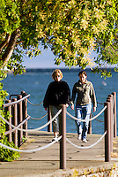 Two friends engaged in conversation stroll along the Songhees walkway into Esquimalt.  Victoria, Vancouver Island, British Columbia, Canada.