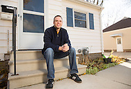 Nick Rhoades sits on the front steps of his house in Waterloo, Iowa on Thursday, November 7, 2013.