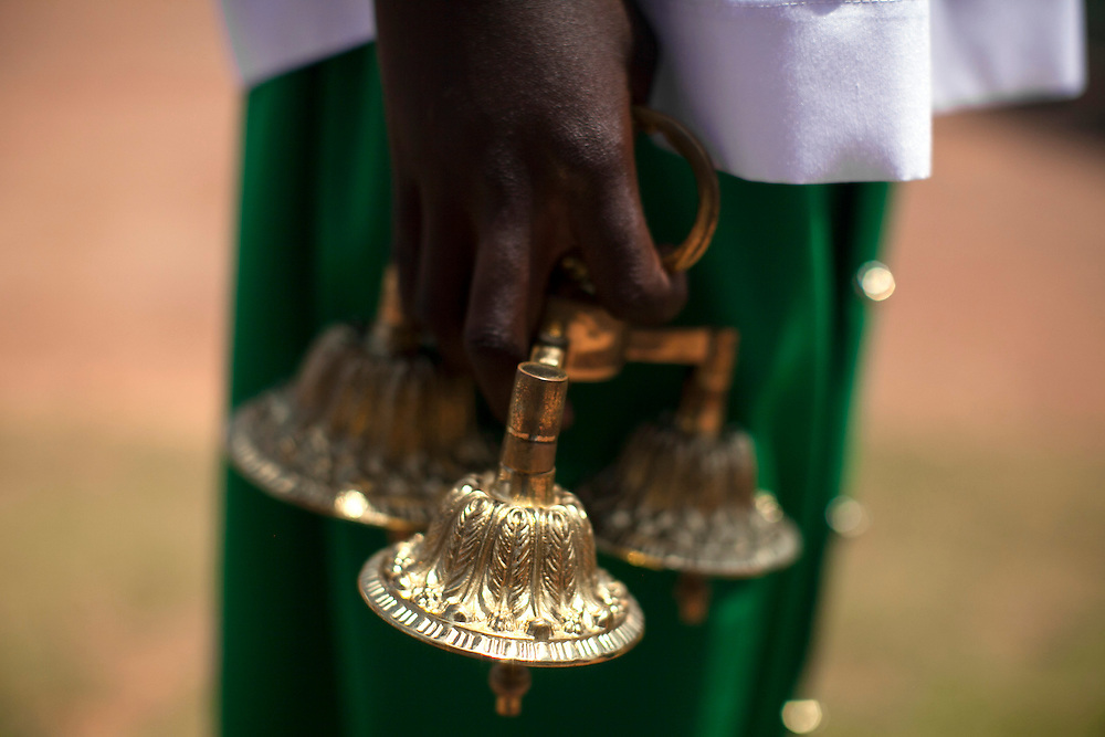 An altar server prepares for the start of mass at The Shrine of Our Lady of Sorrows in Kibeho, Rwanda. This is the only sanctioned Marian sanctuary in Africa. Kibeho's overseers and the Rwandan government hope this place will become a top tourism site. <br /> <br /> Photographed on Sunday, October 26, 2014.<br /> <br /> Photo by Laura Elizabeth Pohl