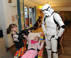 Star Wars, Rachel House, Kinross, 11-12-2016<br /> <br /> People dressed as Star Wars characters to visit children's hospice. Edinburgh 's Capital Sci-Fi Con organiser Keith Armour and other delegates to don costumes and visit children and their families at Rachel House.<br /> <br /> Shannon protects her sister, Erin from a Storm Trooper<br /> <br /> (c) David Wardle | Edinburgh Elite media