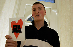 15 year old boy reading a Valentine's Day card on 14 February 2004 UK