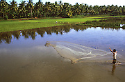 Near Pangandaran, Java, Indonesia, a man net fishes in a fallow field.