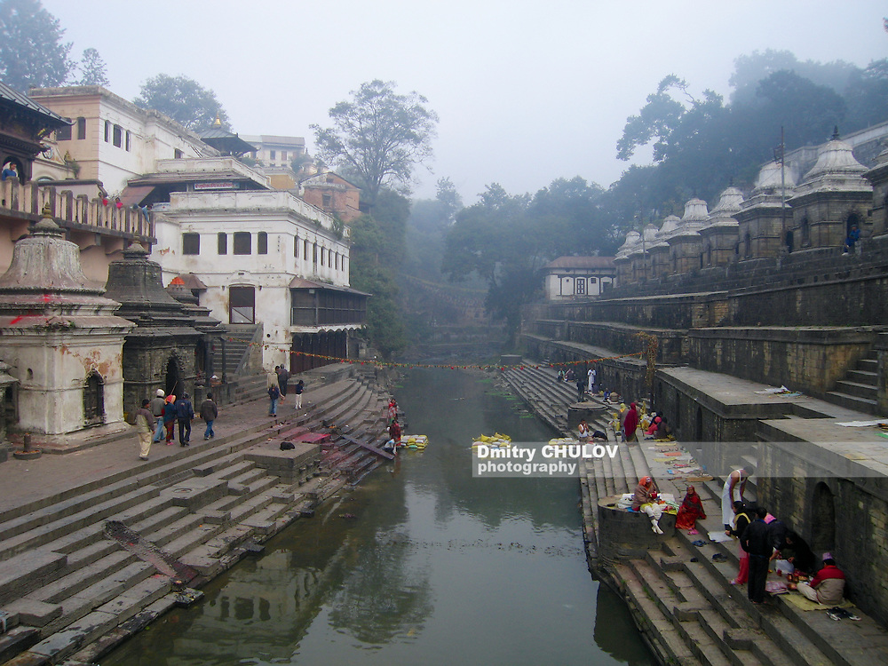 Kathmandu, Nepal - November 27, 2005: Early foggy morning at Hindu temple of Pashupatinath located at the bank of the Bagmati river where traditional cremations take place in Kathmandu, Nepal.