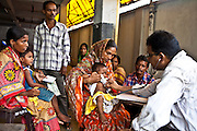 A sick child is examined by a doctor in the CINI health clinic while other families wait their turn. Child In Need Institute (CINI) is based in Kolkata, India. It is a non-governmental organisation (NGO), which provides sustainable development in health, nutrition, education and security for the poorest communities in West Bengal, Jharkhand, Chattisgarh and Madhya Pradesh states.