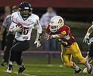 Marion's Nick Kramer (33) dives for Washington's Carl Sivels (25) as he runs with the ball during their game at Thomas Park Field in Marion on Friday, September 20, 2013.