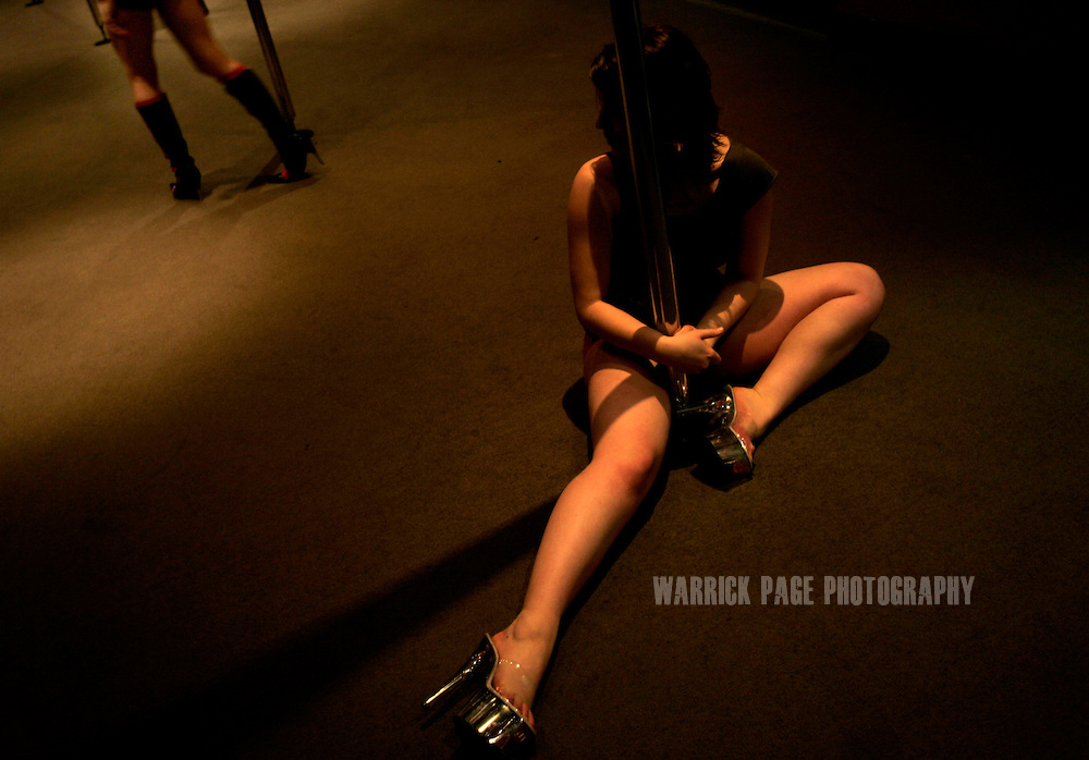 """MELBOURNE, AUSTRALIA - AUGUST 7: Lauren Rui, 18, a university student, rests after performing a move during an advanced pole dancing class at the Imperial Hotel, August 7, 2006, Melbourne, Australia. Lauren was introduced to pole dancing by her boyfriend, who """"recorded a television show on [pole dancing] and encouraged me to take it up"""". Previously reserved for strip clubs, pole dancing is now quickly becoming a new fitness crazy throughout Australia, Europe and the US with thousands of women from all walks of life leaving traditional gymnasiums for the more social and challenging art of pole dancing. Pole dancing for fitness exploded onto the public scene after celebrities such as Angelina Jolie, Jennifer Anniston and Britney Spears professed it was their favourite form of exercise. Classes are often small in numbers giving a more personal atmosphere and strong bonds of friendship are often formed between students and instructors. Instructors claim a noticeable increase in their students' self-confidence after only a few weeks. Most students claim even thought it's a rigorous workout, they're having so much fun it doesn't feel like exercise at all. According to """"Polestars"""", a British company that began setting up classes throughout six Australian cities in 2004,  """"a good session on the pole"""" can burn more calories than at the gym and provide more muscle tone.  (Photo by Warrick Page)"""
