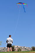 Israel, Haifa, Carmel Beach, Israelis go to the Beach on a warm, sunny day man flies a kite