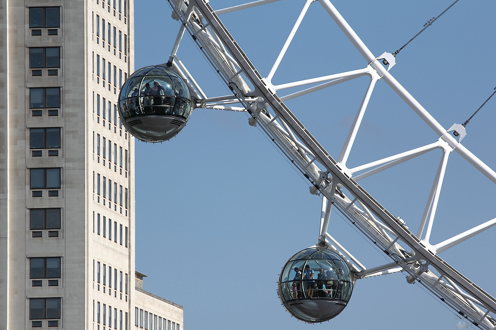 Close-up views of some of The London Eye's pods, seen from the north side of the River Thames; here the pods pass in front of the Shell UK building
