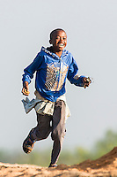 Young Mozambican  boy running with a smile on his face, Limpopo floodplain, Maputo Province, Mozambique
