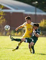 Hopkinton's Tom Echelberger defended by Bow's Robert Lougee stretches to tip the ball with his toe during NHIAA DIvision III Soccer on Tuesday.   (Karen Bobotas/for the Concord Monitor)