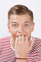 Portrait of amazed young man biting his finger over white background
