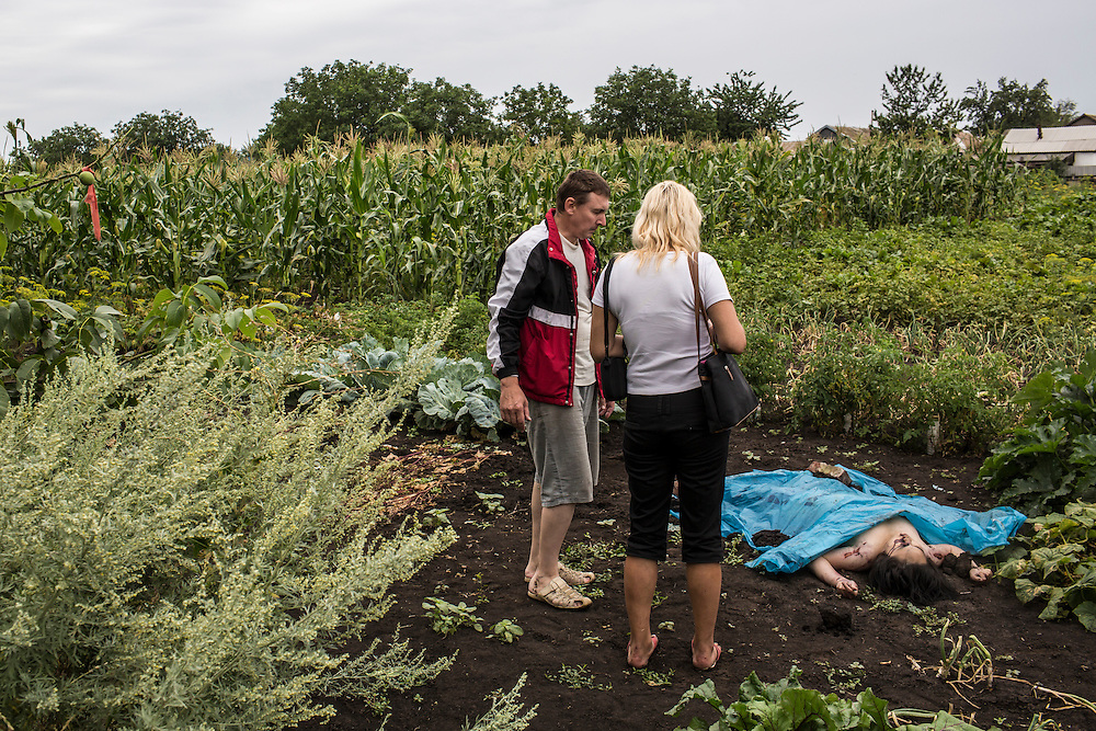 RASSIPNOYE, UKRAINE - JULY 18: People look at the body of a victim of the crash of Malaysia Airlines flight MH17 who landed in a garden on July 18, 2014 in Rassipnoye, Ukraine. Malaysia Airlines flight MH17 travelling from Amsterdam to Kuala Lumpur has crashed on the Ukraine/Russia border near the town of Shaktersk. The Boeing 777 was carrying 280 passengers and 15 crew members. (Photo by Brendan Hoffman/Getty Images) *** Local Caption ***