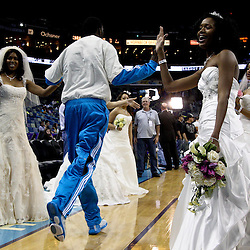 April 3, 2011; New Orleans, LA, USA; New Orleans Hornets players enter the court past women in wedding dresses as part of a promotion for a bridal show before a game against the Indiana Pacers at the New Orleans Arena.    Mandatory Credit: Derick E. Hingle