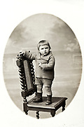 classic studio portrait of a little toddler standing on a chair