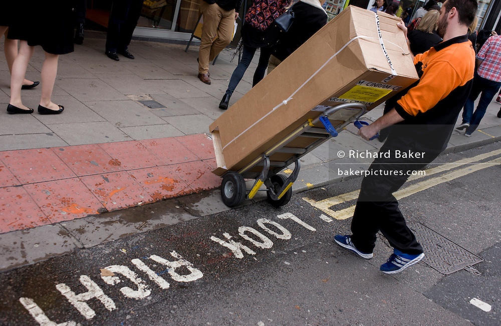 Delivery man struggles to push awkward trolly and tall, verticle box over road crossing.
