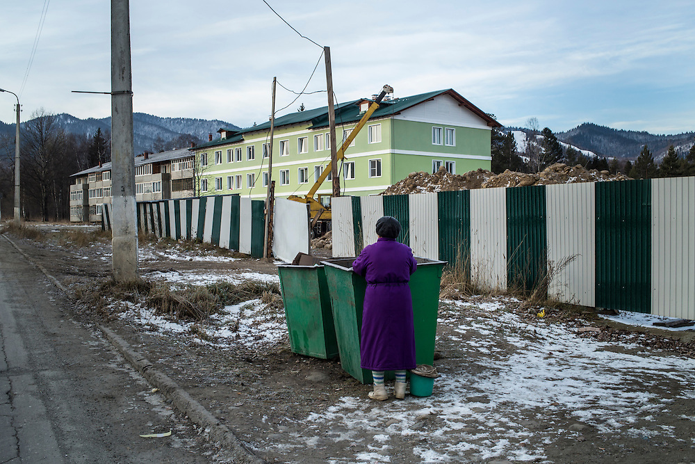 A woman looks through a dumpster on Wednesday, October 23, 2013 in Baikalsk, Russia.