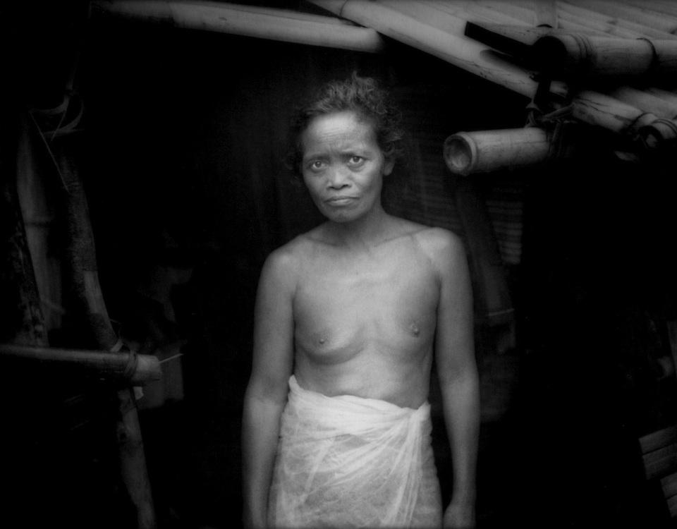 Village headman Pok's wife in the doorway to the kitchen of her hut, Sawa, Sierra Madre Mountains, Luzon, Philippines.