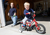 Chris Kotzian (L) watches his son Adam, 6 hop on his bike at his home in Thornton, Colorado March 25, 2010.  Chris and Adam are both achondroplasia dwarfs. Chris is active in the Little People of America, the only dwarfism support organization that includes all 200+ forms of dwarfism.  REUTERS/Rick Wilking (UNITED STATES)