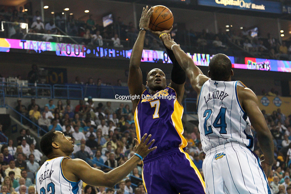 April 24, 2011; New Orleans, LA, USA; Los Angeles Lakers power forward Lamar Odom (7) shoots over New Orleans Hornets power forward Carl Landry (24) and shooting guard Willie Green (33) during the first quarter in game four of the first round of the 2011 NBA playoffs at the New Orleans Arena.    Mandatory Credit: Derick E. Hingle