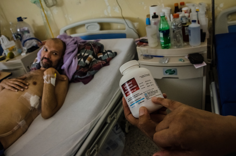 CARACAS, VENEZUELA - JANUARY 22, 2015: Nohelyth Rodriguez, the wife of AIDS patient Franco Bigotti, 47, shows a visitor the antiretroviral medicine her husband takes, which is manufactured in India, and given to him at a state-run hospital outside of Caracas. A few months ago, Mr. Bigotti and fellow AIDS patients at this hospital went nearly three months without their antiretroviral medicines, that the government provides them free-of charge when they're available.  Doctors at the hospital said that because of the shortages, they are working with a bare minimum of supplies, and that patients often die because of a lack of resources. Despite being a petro-state with one of the largest oil reserves in the world, basic and advanced medical supplies from gauze and surgical gloves, to heart stints, are difficult to find in hospitals and pharmacies across Venezuela.