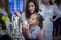 Chana Federman lights the first of several candles with help from her mother, Henya.  Henya Federman of Chabad Lubavitch of the Virgin Islands, lights candles before dinner with family and friends to usher in the Rosh Hashanah, the Jewish New Year.  © Aisha-Zakiya Boyd