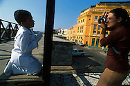 Un niño vestido de primera comunión, posa arrodillado con sus manos juntas, sobre la muralla. Y en frente un mujer encuadra su cámara para registrar el momento. Cartagena de Indias,  2001 (Ramón Lepage / Orinoquiaphoto)     The fortified wall of Cartagena is in excellent condition and stretches more-or-less unbroken round a good portion of the Old Town. It is a pleasure for locals well as visitors to walk and observe the colonial architecture and excellent view of the Caribbean ocean..