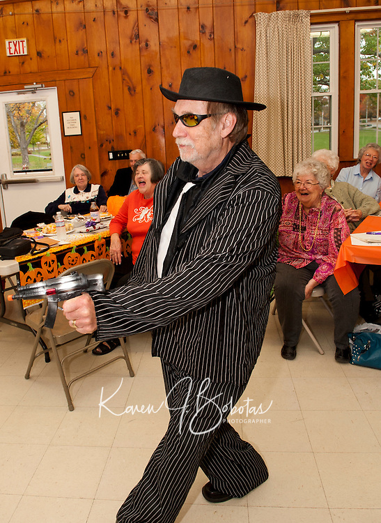 Peter Fijalkowski dressed as the infamous gangster Al Capone takes a shot at fellow members of the Laconia Elders Friendship Club with his plastic toy gun during their annual Halloween Parade at Leavitt Park clubhouse in Lakeport Wednesday afternoon.  (Karen Bobotas/for the Laconia Daily Sun)