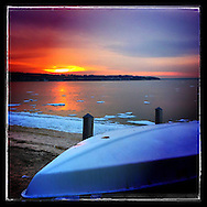 Sea Cliff,  NY, March 16, 2015:  The sun sets at Sea Cliff beach in Nassau County, Long Island.  An overturned rowboat sits on a rack waiting for warmer weather and for  the ice to melt in Hempstead Harbor.         © Audrey C. Tiernan