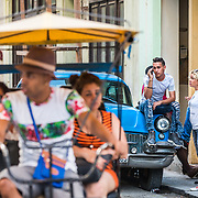 03/10/2017  OLD HAVANA, CUBA     A sits on the hood of his car while a pedicab rides by in Old Havana, Cuba.  (Aram Boghosian for The New Orleans Advocate)