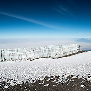 Glaciers of ice are permanently on the summit of Mt Kilimanjaro, although they are diminishing rapidly with climate change. At right of frame in the distance is the peak of Mt Meru poking through the clouds.