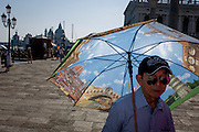 Chinese tourist with umbrella in Piazza San Marco, Venice, Italy