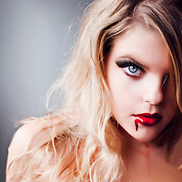 Close up of young woman with blonde hair and red blood running from mouth like vampire