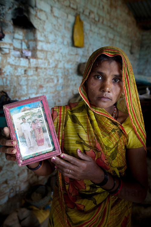 Siarani hold the photograph of her husband Pratipal Singh who committed suicide due to hunger the previous year in  Chandauli in Mahoba district, Uttar Pradesh, India, on Thursday September 10, 2009. Photographer: Prashanth Vishwanathan/Action Aid