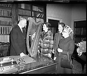"""Presentation of Harp to President DeValera..1972..29.12.1972..12.29.1972..29th December 1972..Mrs Julia Fennell presented a harp to President DeValera as a gift to Áras an Uachtaráin. She presented the harp on behalf of her late husband Mr Thomas J Fennell and herself..The harp was manufactured in 1835 at the firm of Robinson and Russell,westmoreland Street,Dublin. the harp is 36ins high and has 33 strings. It will be retained in an exhibition case bearing the inscription """"Tomas O'Fionnghaill agus Sile Ui Fhionnghail,Baile Atha Cliath, a bhronn ar Áras an Uachtaráin,1972"""".(Presented to Áras an Uachtaráin by Thomas and Julia Fennell,Dublin 1972)..Image shows President DeValera accepting the harp from Mrs Julia Fennell who was accompanied by her daughters Dr Geraldine Fennell and Ms Rosemary Fennell."""
