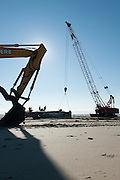 Workers labor to remove a cement floating boat dock that had drifted across the Pacific Ocean resulting from the 2011 Japanese tsunami.