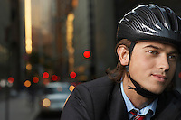 Smiling man wearing cycling helmet on street close-up portrait