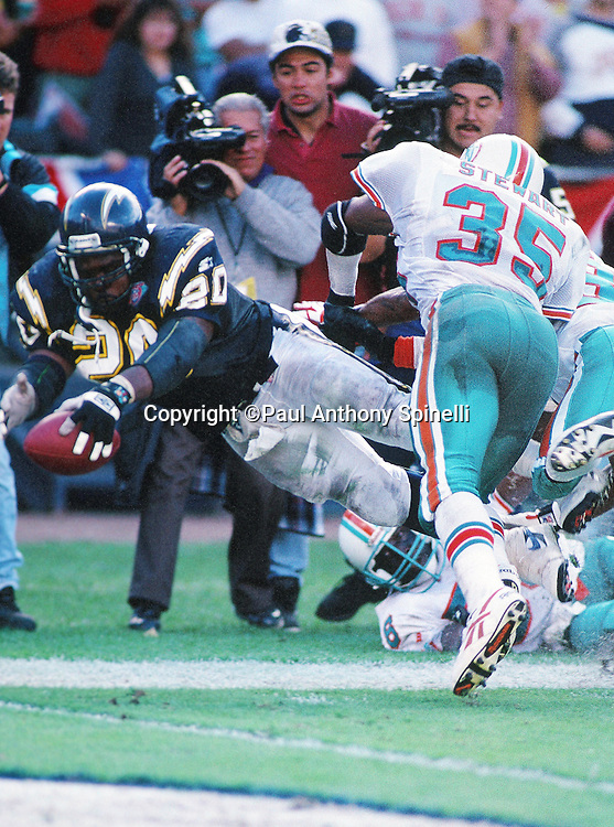San Diego Chargers running back Natrone Means (20) dives for the end zone while Miami Dolphins safety Michael Stewart (35) and fellow Dolphins teammates try to knock him out of bounds during the NFL AFC Divisional playoff football game against the Miami Dolphins on Jan. 8, 1995, in San Diego. The Chargers won the game 22-21. (©Paul Anthony Spinelli)
