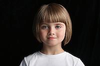 Girl (5-6) on black background portrait close-up