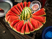 "25 OCTOBER 2015 - INSEIN, MYANMAR:  Watermelon for sale by the slice at Danyin Market (also known as Da Nyin) in Insein, Myanmar, about 90 minutes from Yangon. Vendors in the market sell just about everything people in the area need, but mostly it's a ""wet market"" with fruits, vegetables and meats. Most people in Myanmar still do not have refrigerators in their homes, so people go to market almost every day.    PHOTO BY JACK KURTZ"