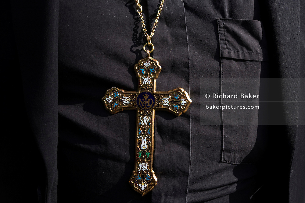 A pectoral crucifix cross worn by an anonymous Anglican (Protestant Church of England) Bishop during Pope Benedict XVI's papal tour of Britain 2010, the first visit by a pontiff since 1982. Taxpayers footed the £10m bill for non-religious elements, which largely angered a nation still reeling from the financial crisis. Pope Benedict XVI is the head of the biggest Christian denomination in the world, some one billion Roman Catholics, or one in six people. In Britain there are about five million Catholics but only a quarter of Catholics regularly attend Sunday Mass and some churches have closed owing to spending cuts.
