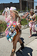 Brooklyn, NY - 18 June 2016. The Naked Cowgirl, oftenfound in Times Square, with a pink seashell bikini top, and carrying her guitar, rusging to take her place in the parade.