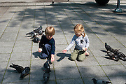 Boy & girl feed pigeons along Gediminas Prospect/Gedimino Prospektas, Vilnius, Lithuanai; MR on file