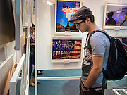 19 JULY 2013 - BANGKOK, THAILAND:   A tourist looks at photos hanging in an exhibit in CentralWorld in Bangkok. The US Embassy in Bangkok sponsored the photo exhibit, which celebrates 180 years of US-Thai diplomatic relations. There are 180 photos hanging in the show, 90 by American photographers in Thailand and 90 by Thai photographers in the United States. The show, which opened July 19, is hanging in CentralWorld, a large mall in Bangkok, and is touring Thailand when it concludes its Bangkok run on July 21.   PHOTO BY JACK KURTZ
