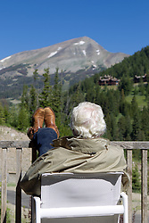 back of a mature man sitting in an outdoor chair with his feet up as he looks towards a mountain in Montana