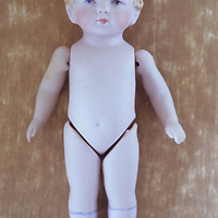 Close up from above of small naked traditional baby doll with articulated limbs and painted socks and shoes lying on rough board